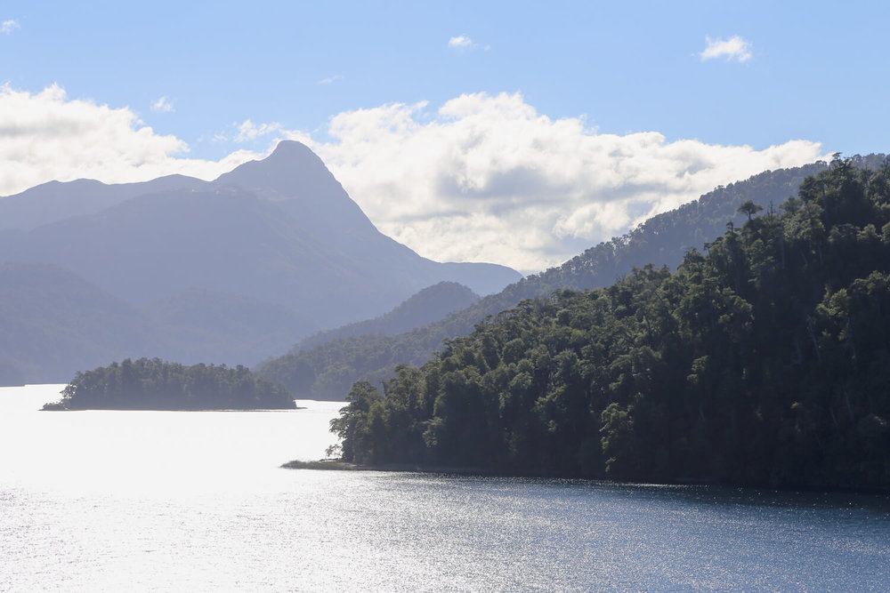 A lake next to tree covered mountains on the Road of the Seven Lakes Argentina
