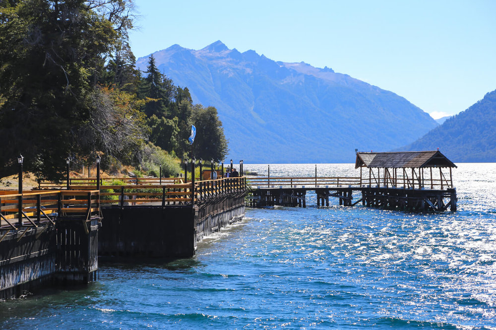 A pier extends over a large blue lake with a mountain in the background on the Ruta los Siete Lagos Argentina