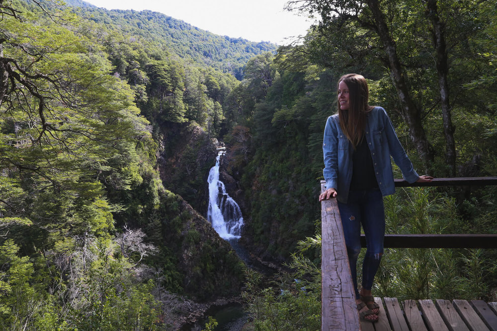 A woman stands on a deck overlooking a waterfall and green forest insan martin de los andes argentina