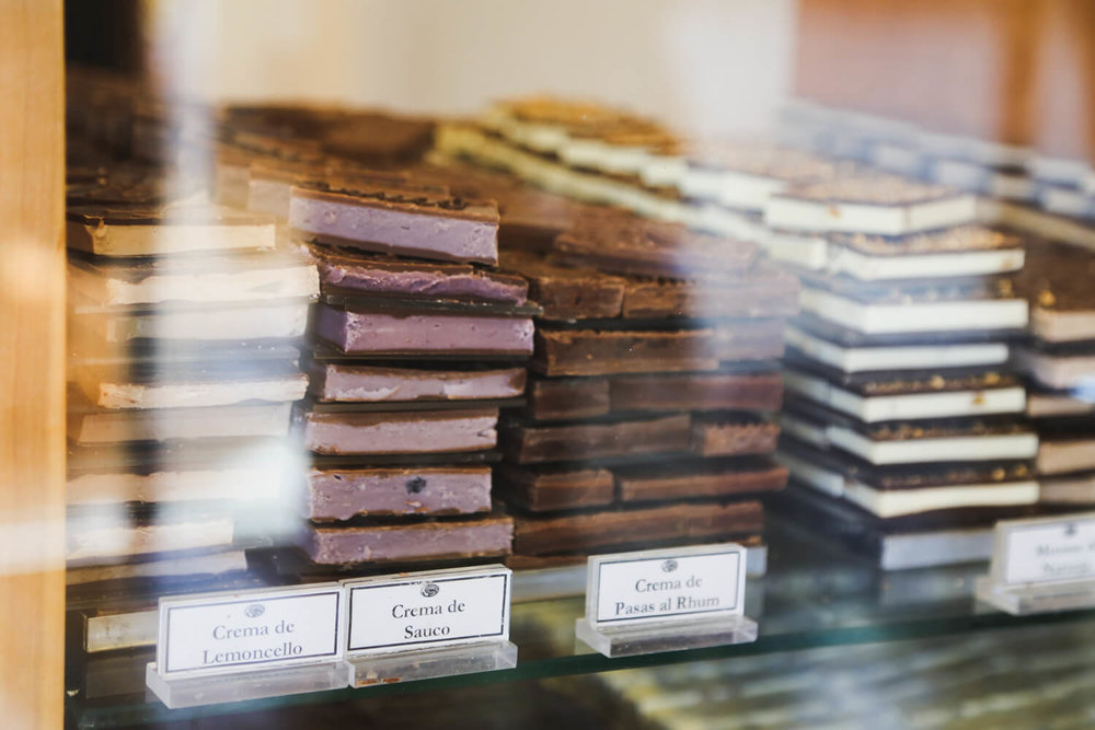 Stacks of chocolate filled with local Patagonian flavors sit behind a glass divider in  san martin de los andes argentina