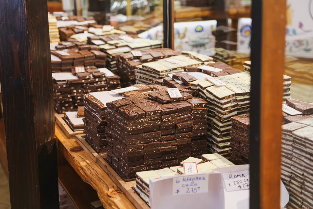 Piles of chocolate sit on a shelf in a chocolate shop in  san martin de los andes argentina