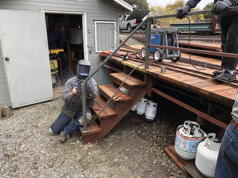 Tom (with Carl supervising above) welds hand railing on the engine house deck