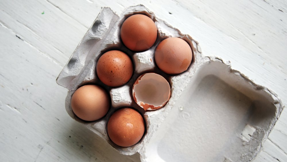 Carton of brown eggs on a white table.