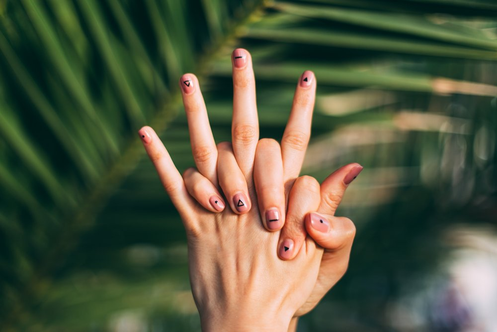 Two hands with painted nails intertwined in front of tropical leaves.