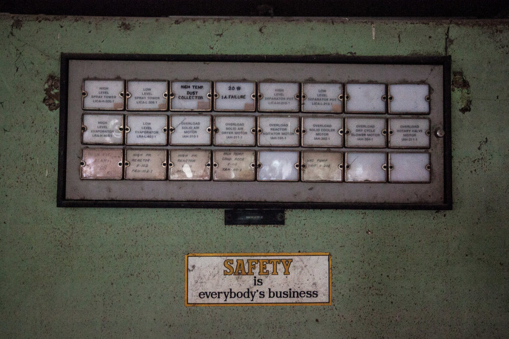 "The dials responsible for notifying the status of the different methyl isocyanate tanks in the control room. A sticker stating ""safety is everybody's business""."
