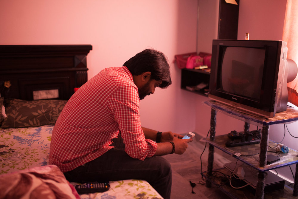 A 30 year-old management consultant, who has been denied an H1-B visa waits for a work call in his bedroom.