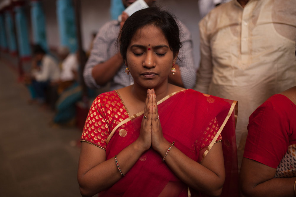 A devotee prays as she walks in the Chilkur Balaji Temple, known as the visa temple.