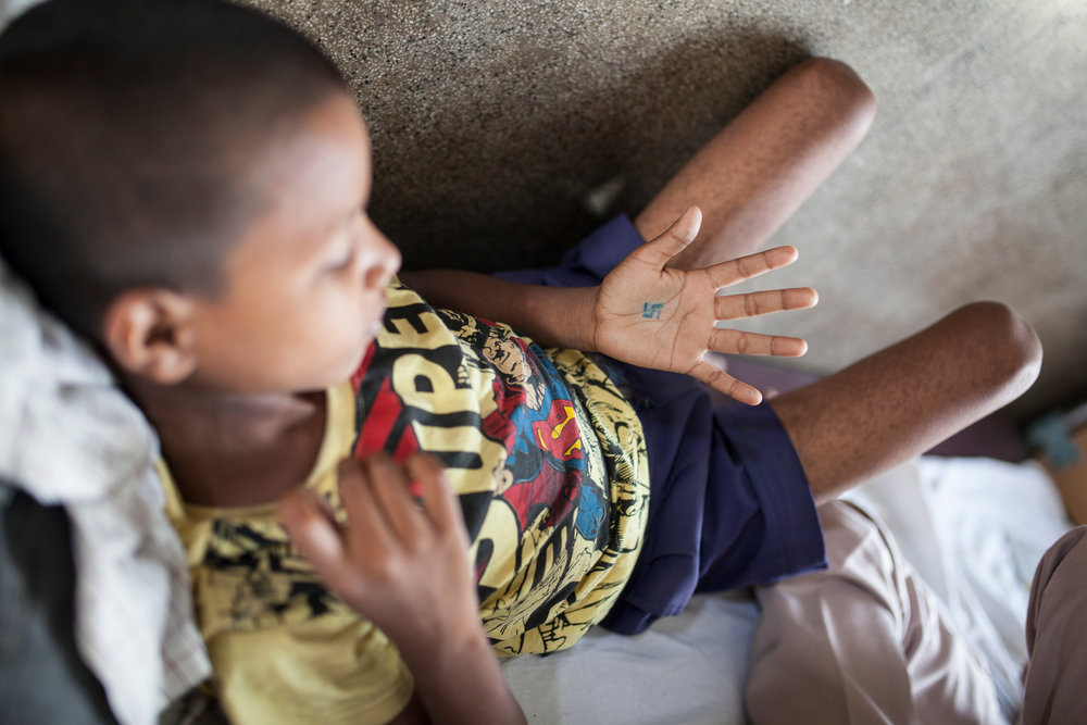 In Hinduism, the swastika is a sign of good will and luck. Ranjit has drawn one on his hand a few hours before leaving the hospital.