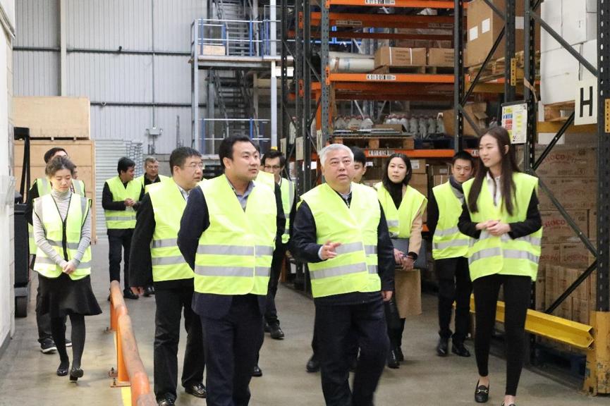 天津市政协主席盛茂林与飞翔公司董事长田小青在参观公司仓储区域期间交谈