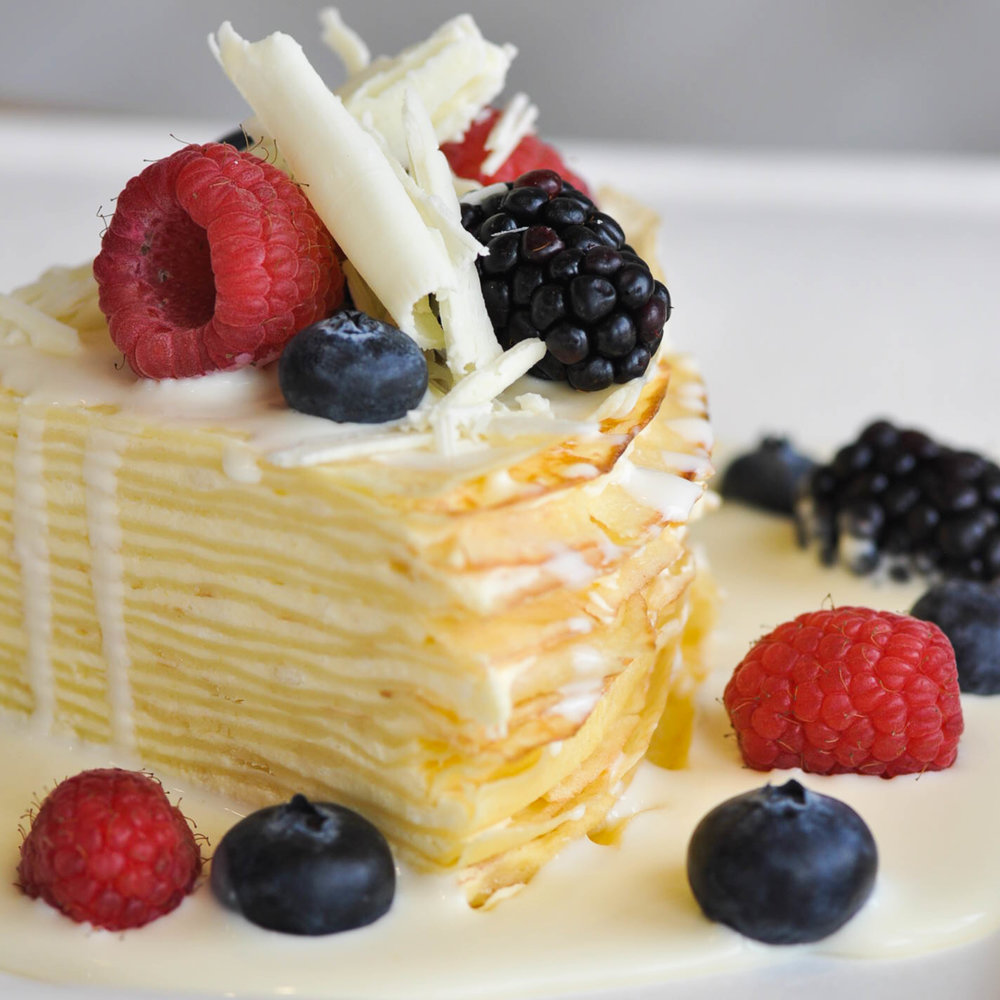 Lemon Stack |  layers of homemade lemon mousse and delicate crepes topped with a white chocolate sauce and fresh berries