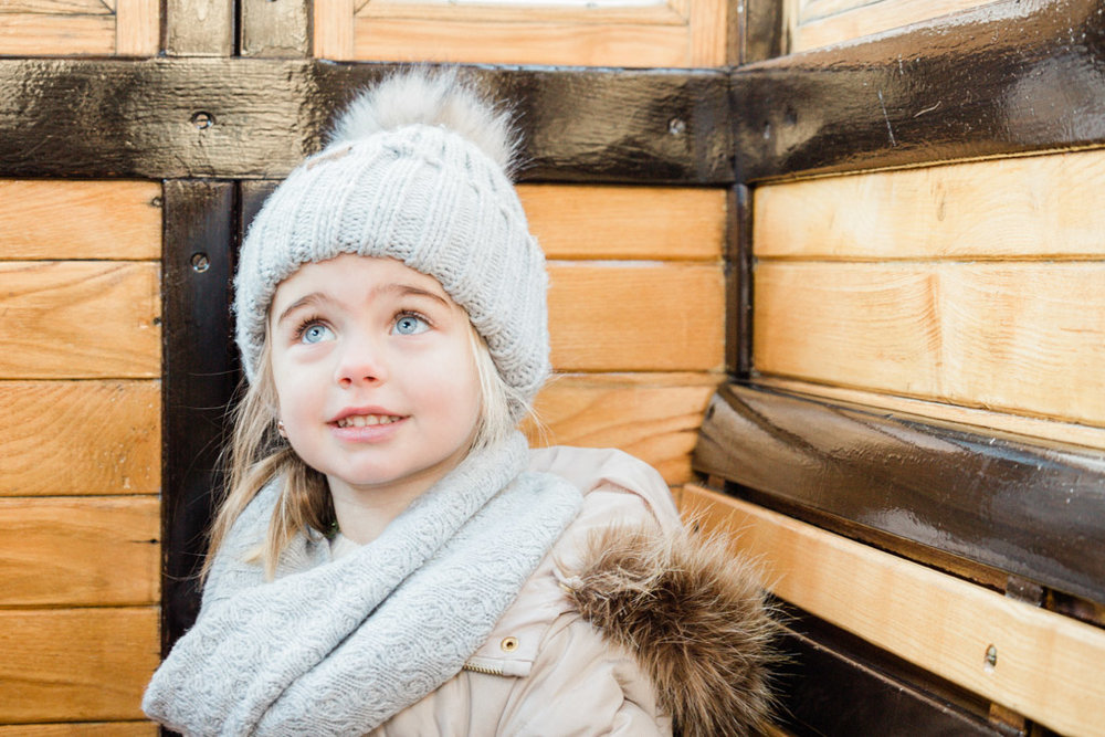 Little girl in gray winter hat and scarf riding Budapest funicular.