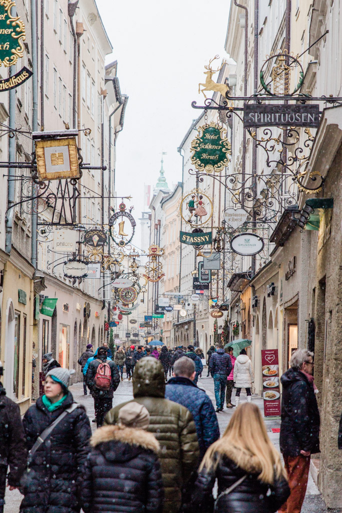 People shopping on Getreidgasse filled with old decorative iron signs while the snow is falling.