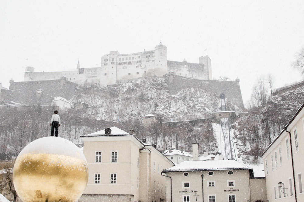 Salzburg Castle covered in snow upon a hill overlooking the town.