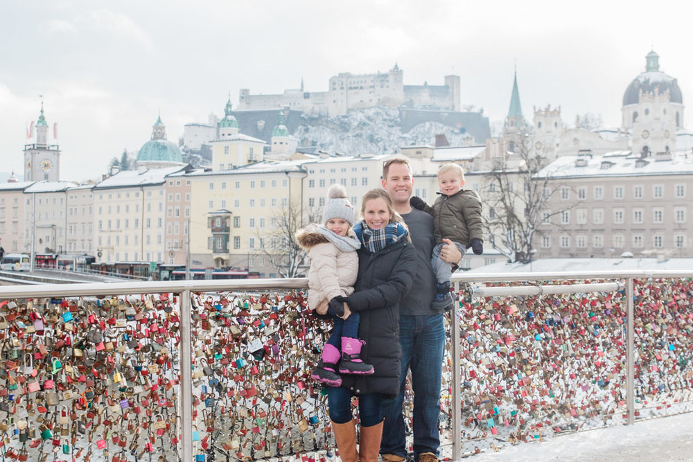 Family picture on a lock-covered bridge with snowy Salzburg in the background.