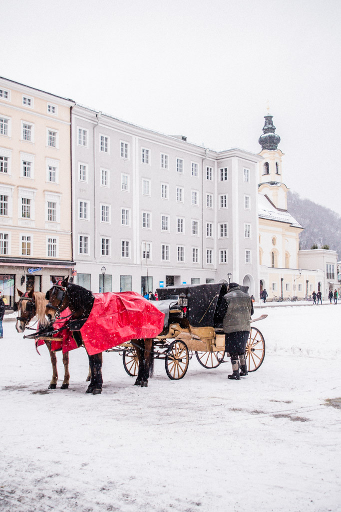 Snowy Salzburg with horse carriage and pastel-colored buildings.