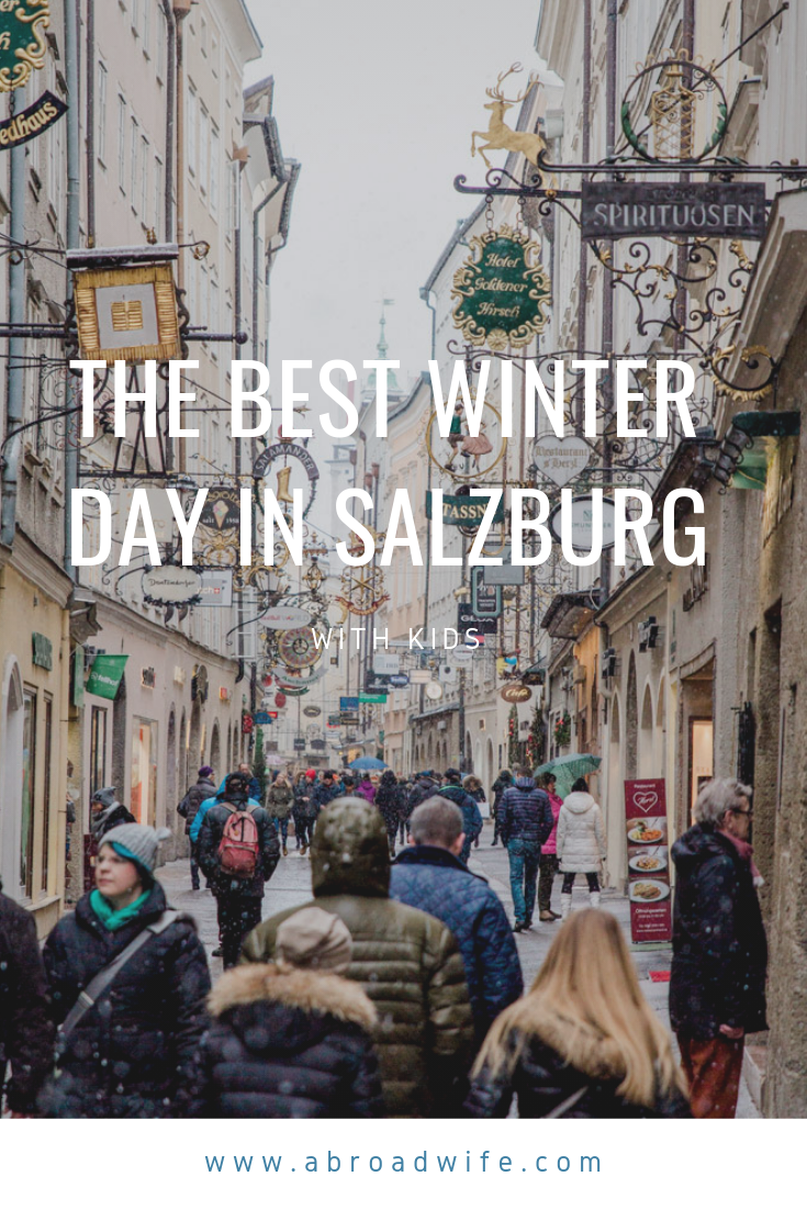 """People shopping on a snowy street in Salzburg, Austria. Text overlay """"The Best Winter Day in Salzburg"""""""