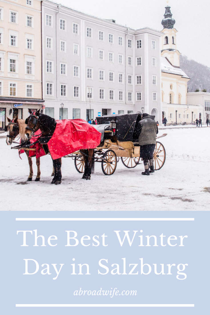 Horse carriage in snowy Salzburg, Austria in front of pastel buildings.