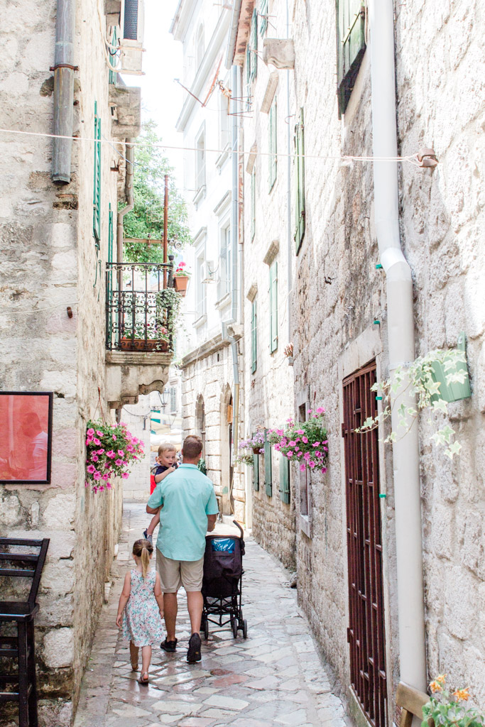 Dad and kids walking the white stone streets of Kotor, Montenegro.