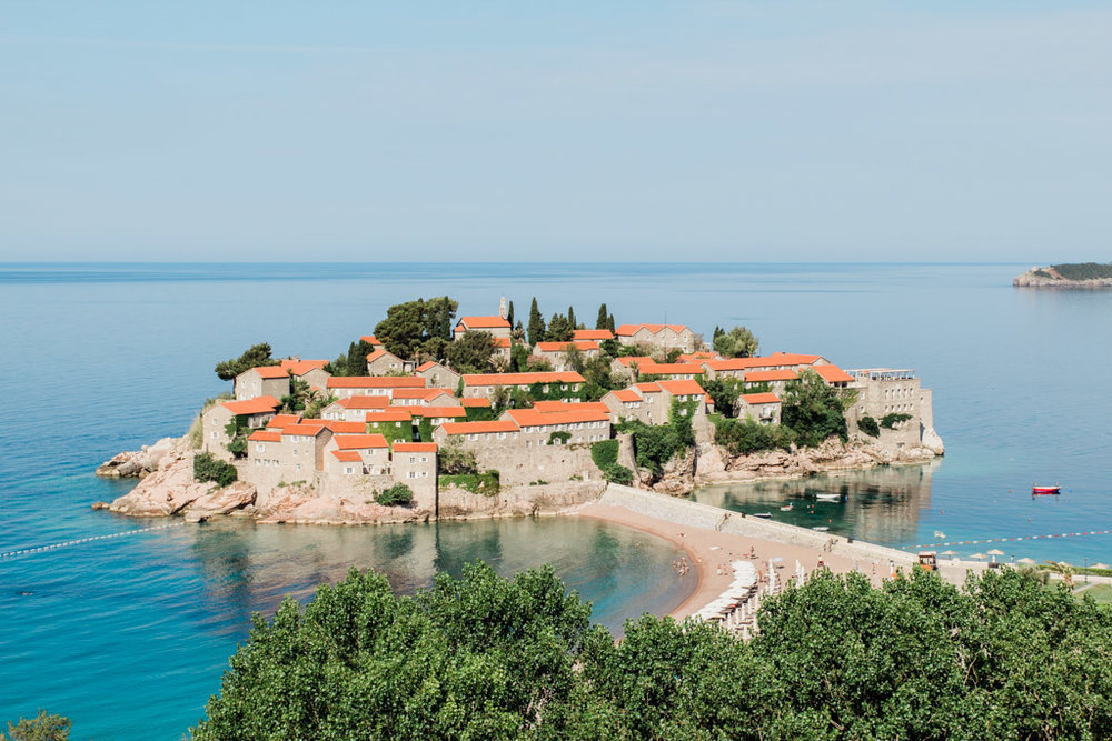 Small peninsula of Sveti Stefan with pink beach, white buildings, orange roofs, and bright blue water!