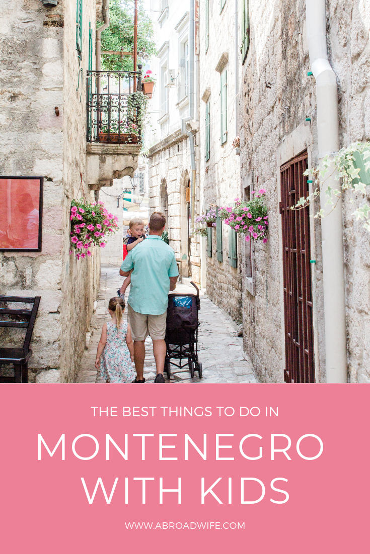 Dad with small children walking throug the white stoned streets of Kotor, Montenegro.