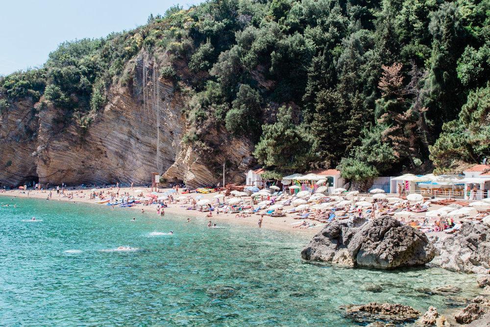 Turquoise water of Mogren Beach, full of people swimming and sunbathing in Budva, Montenegro.