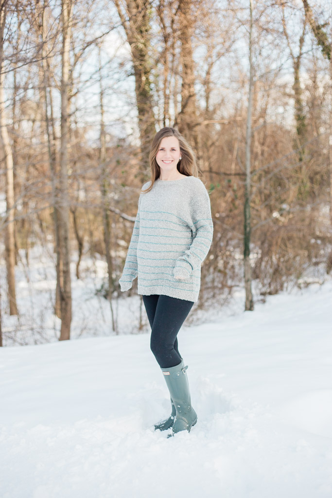 Woman 32 weeks pregnant in gray maternity sweater, leggings, and Hunter rain boots standing in snow.