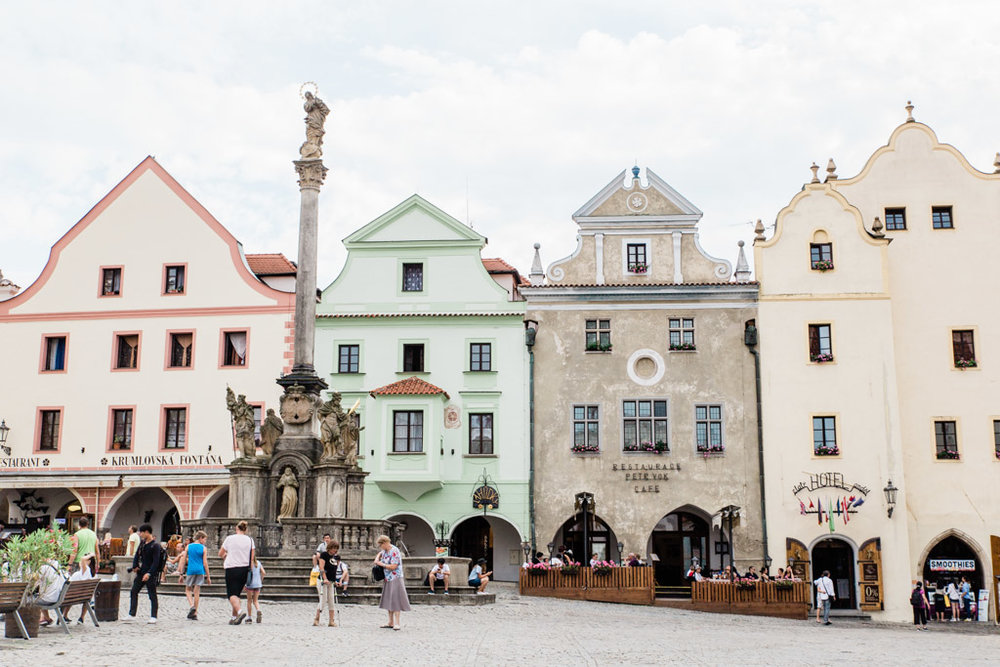 Pastel colored buildings and decorative fountain in Cesky Krumlov's main square.