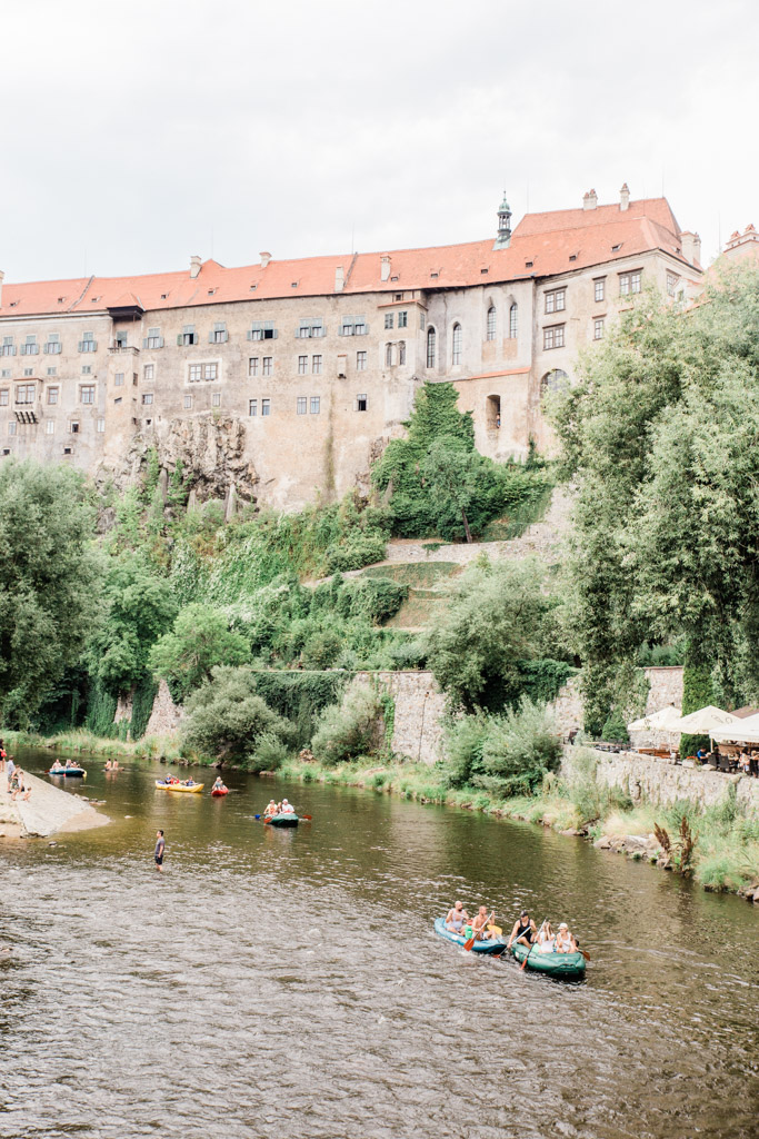 Cesky Krumlov Castle above Vltava River where people are rafting on the water.