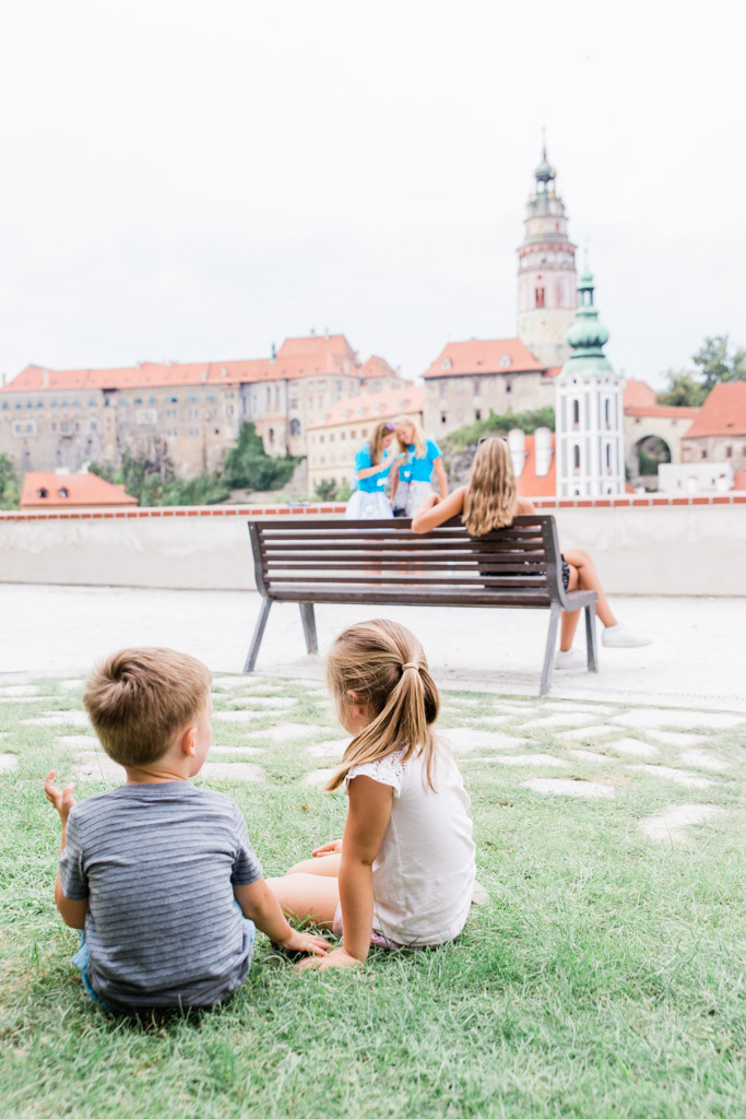 Brother and sister sitting on grass at viewpoint looking at Cesky Krumlov's castle.