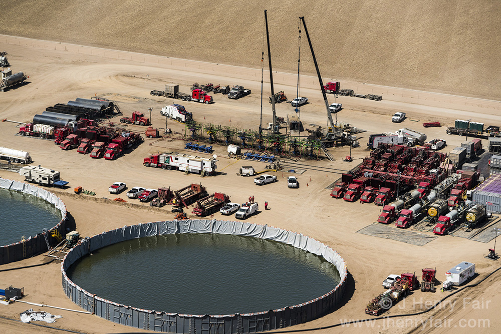 Compressor trucks, well-heads and water reservoirs at fracking site, Boulder, CO