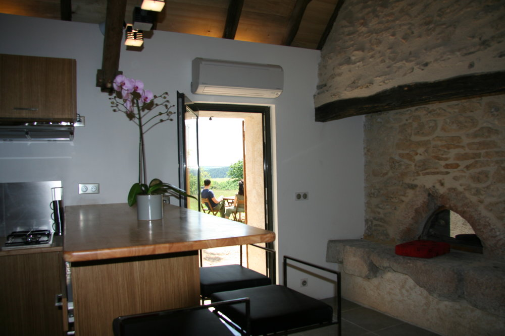 Le Cocon - Vue exterieure de la porte d'entrée avec cuisine à gauche et cheminée à droite.JPG