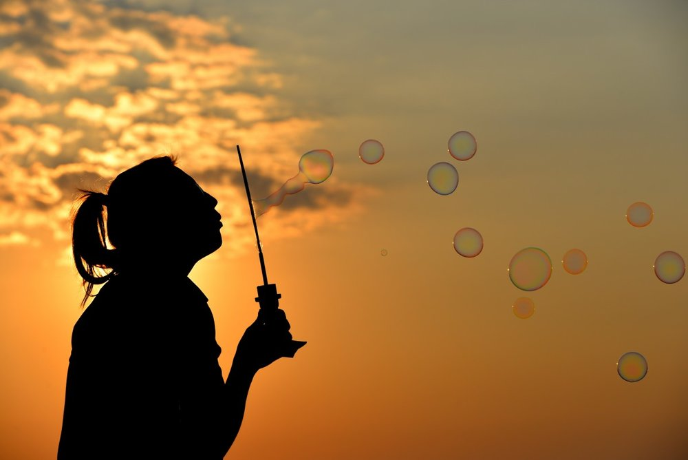 Woman blowing bubbles. No one has to live with the weight of past trauma or depression