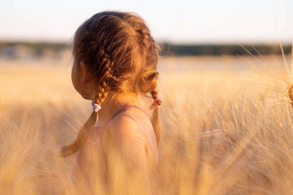 A child in a field with golden wheat growing around her. Tipi helps her feel calm and helps parents care for her emotional struggles anger, fear, sadness.