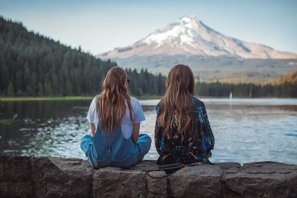 Two women enjoy a mountain view while sitting together lakeside. Enjoy life with emotional freedom, relieve stress, increase self confidence.