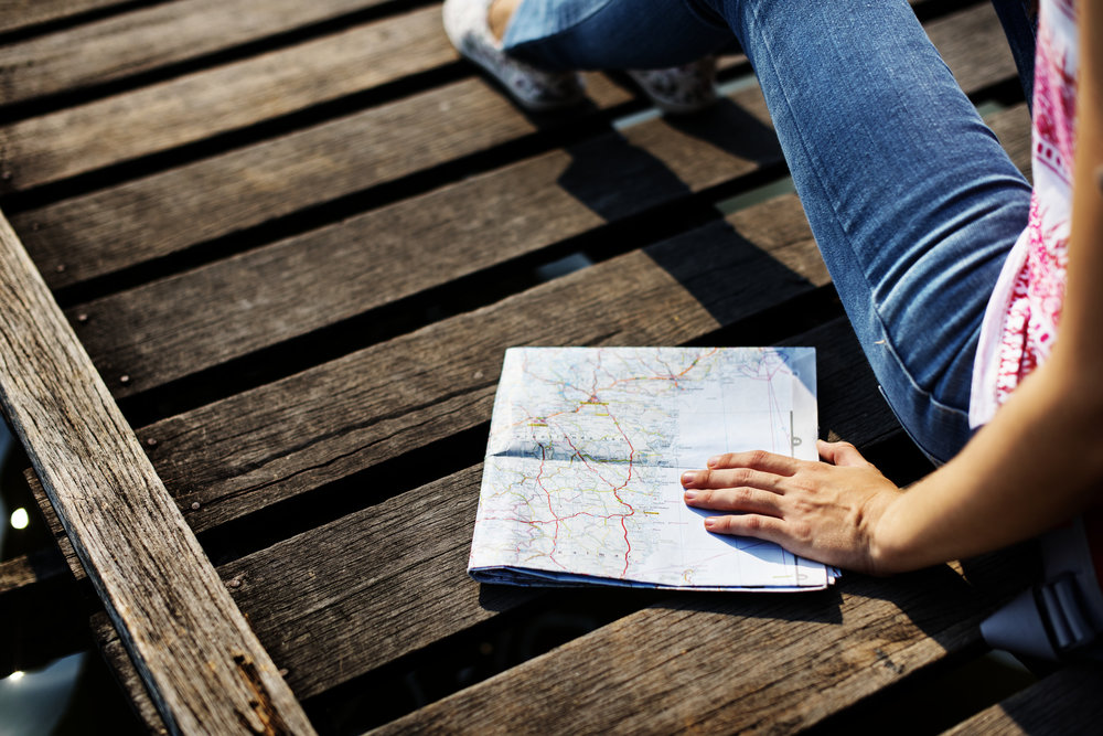 Woman with a map on a dock. Plan to live life fully and overcome fear, anxiety, phobias. Increase self confidence.