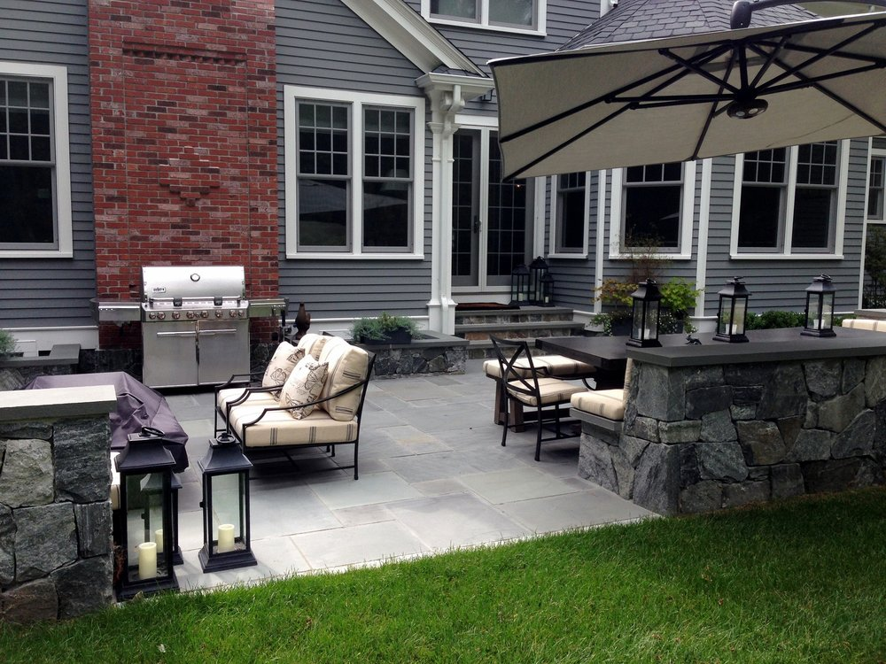 Landscape design with patio pavers and outdoor kitchen in Belmont, MA