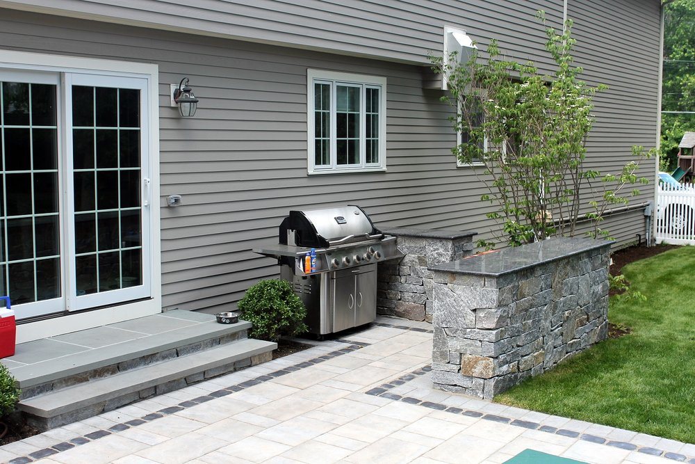 Bluestone patio with outdoor kitchen in Newton, MA