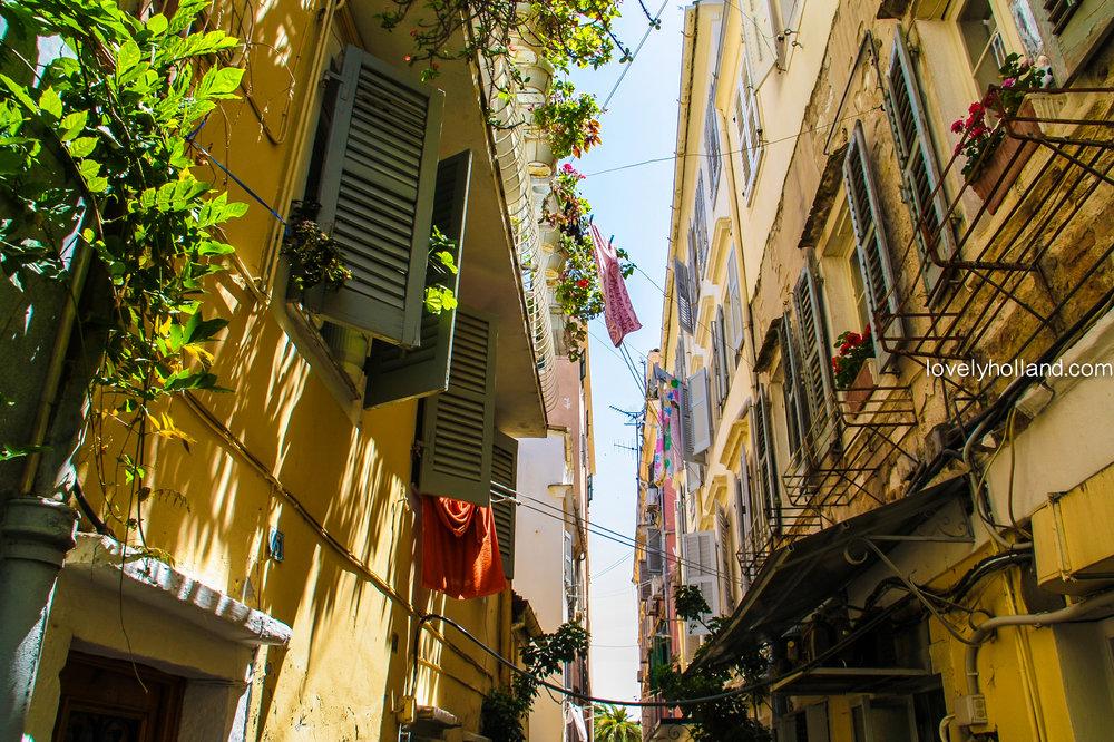經典南歐街景:可愛百葉窗,黃色外牆,一排排曬著太陽的衣服。