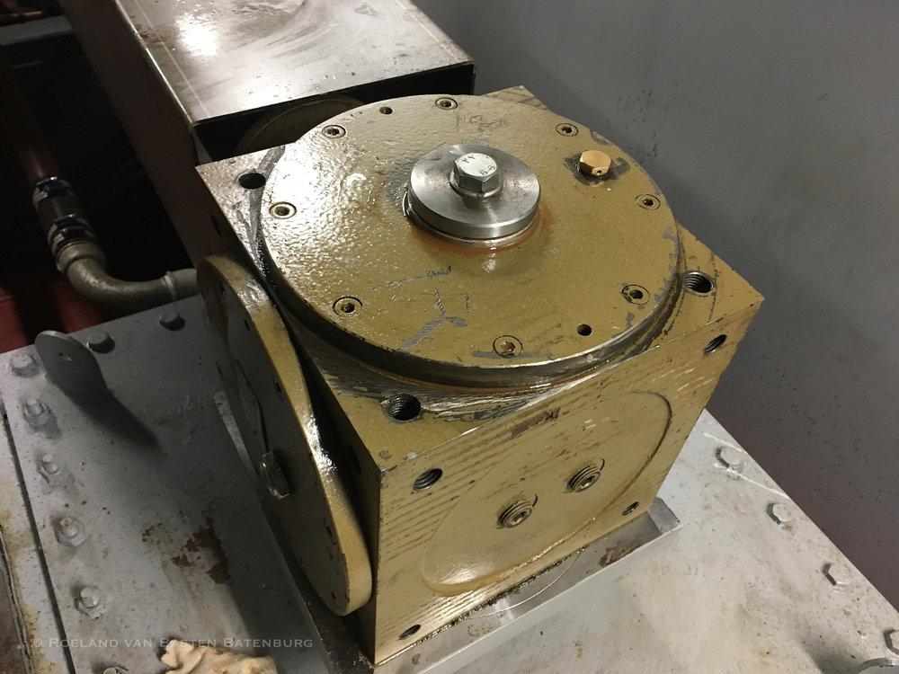 De tandwielkast van de kopschroef. Hij lekt olie via de zilverkleurige ring aan de bovenkant.