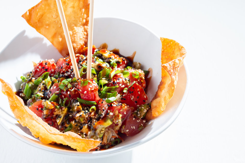 ahi tuna poke bowl - Soy sesame ginger, marinated, Ahi tuna tossed with fresh avocado, green onions, and sesame seeds over Wakame seaweed salad served with crispy Wonton chips.