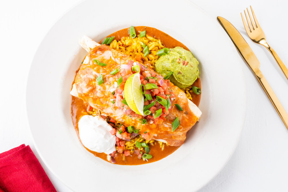 BLACKENED SEAFOOD BURRITO - Lightly blackened seafood, black beans, mixed jack cheeses, homemade enchilada sauce, served with sour cream, guacamole, and Pico de Gallo salsa over a bed of yellow rice.