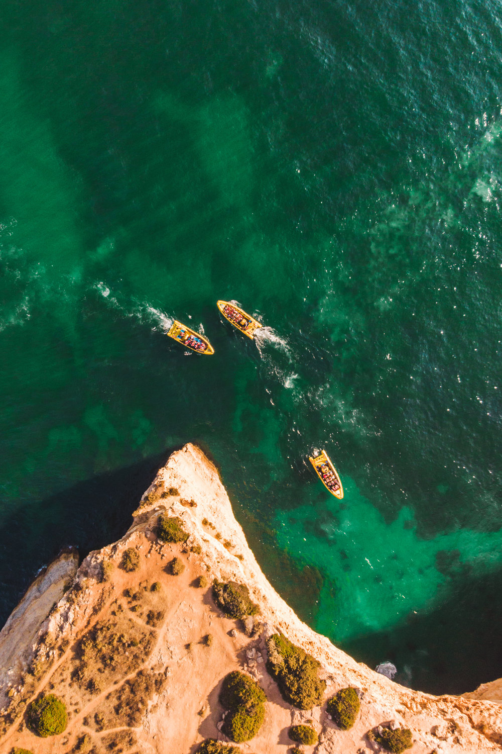 Aerial view of a group of boats near the cliff.