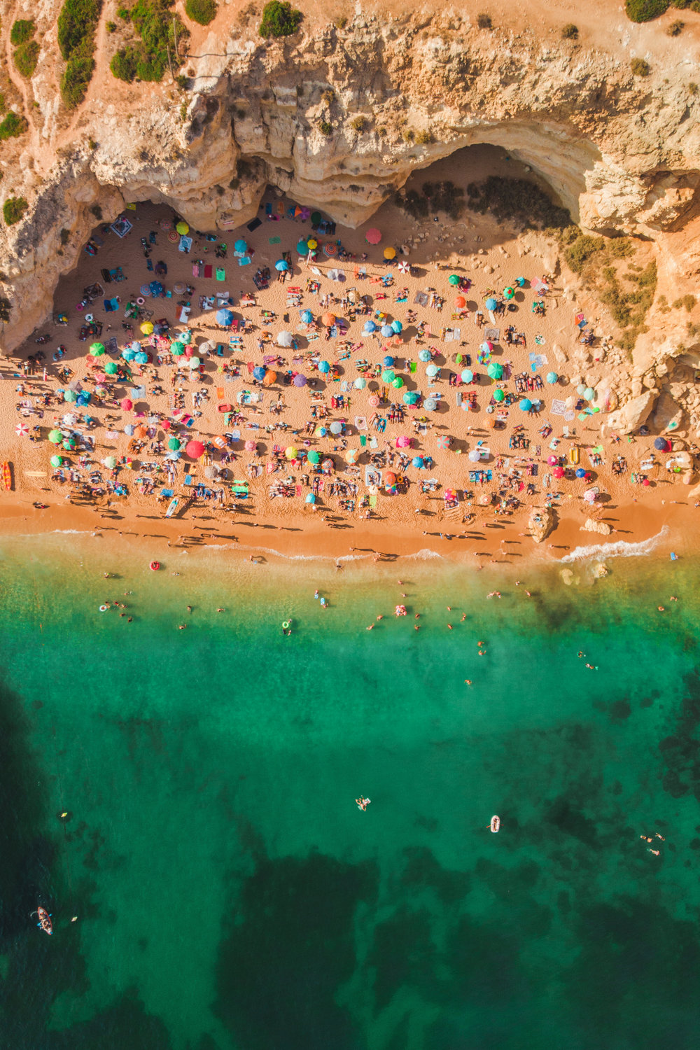 Aerial view of cliff beach with a lot of people and summer umbrelas.