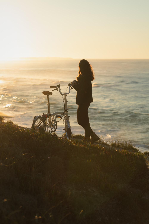 Girl at sunset with Brompton bike.