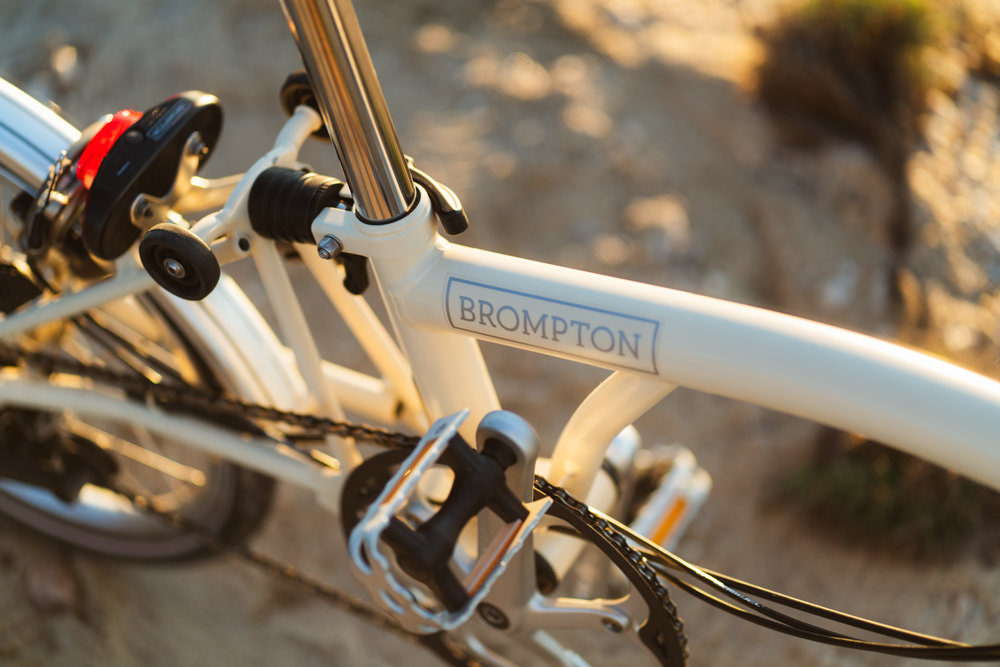 Brompton bike detail with logo at sunset.