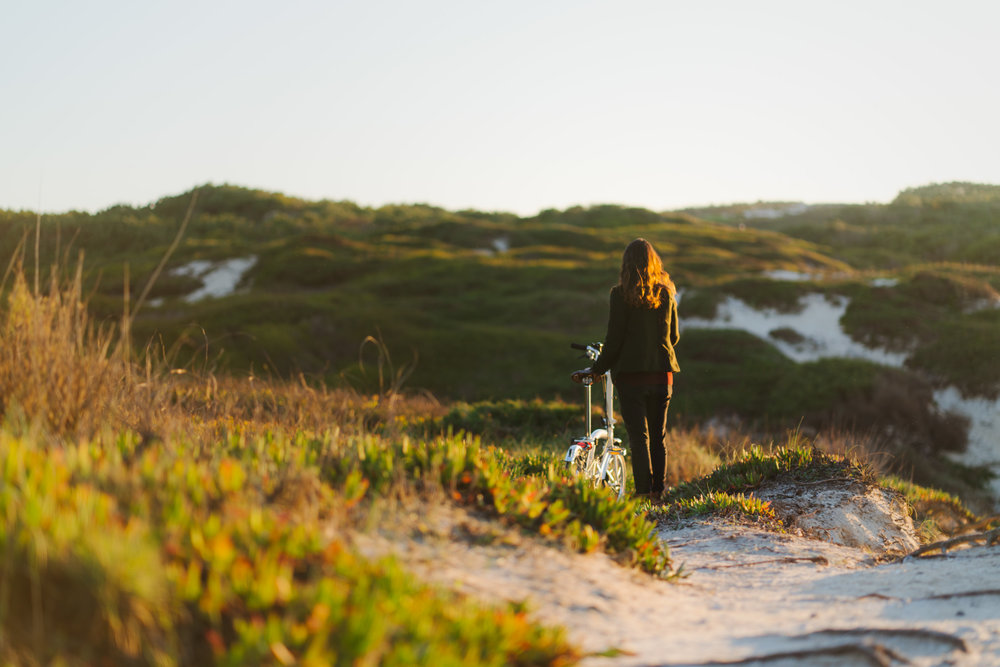 Girl walking with Brompton bike over beach dunes at sunset.