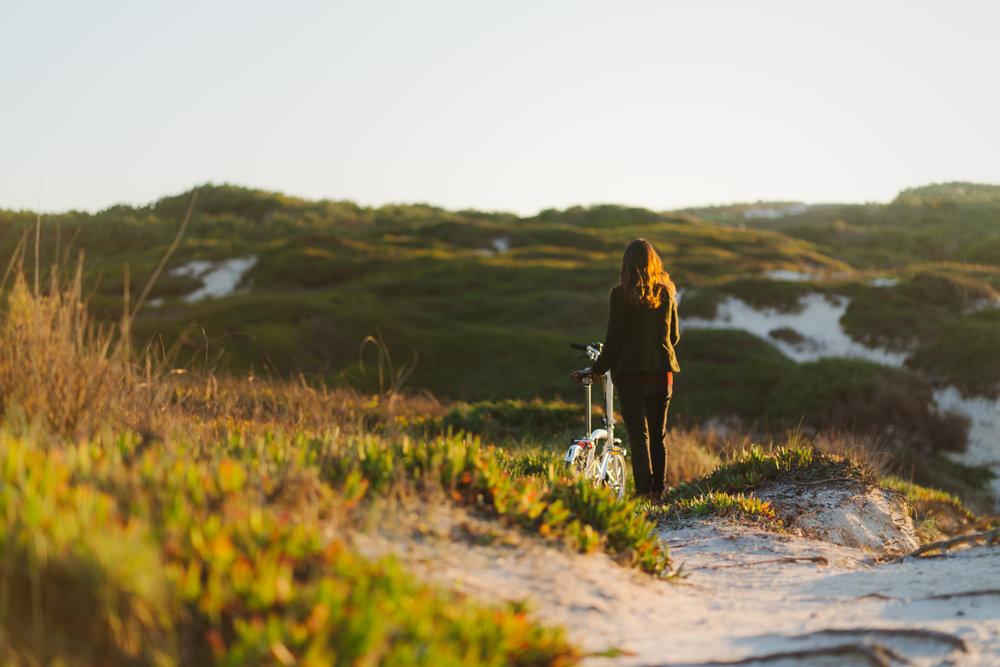 Girl walking with Brompton bike over beach dunes at sunset.