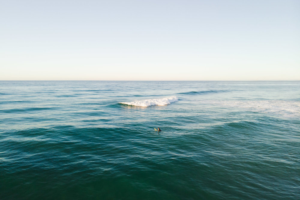 Blue ocean with surfer and wave breaking at sunset.
