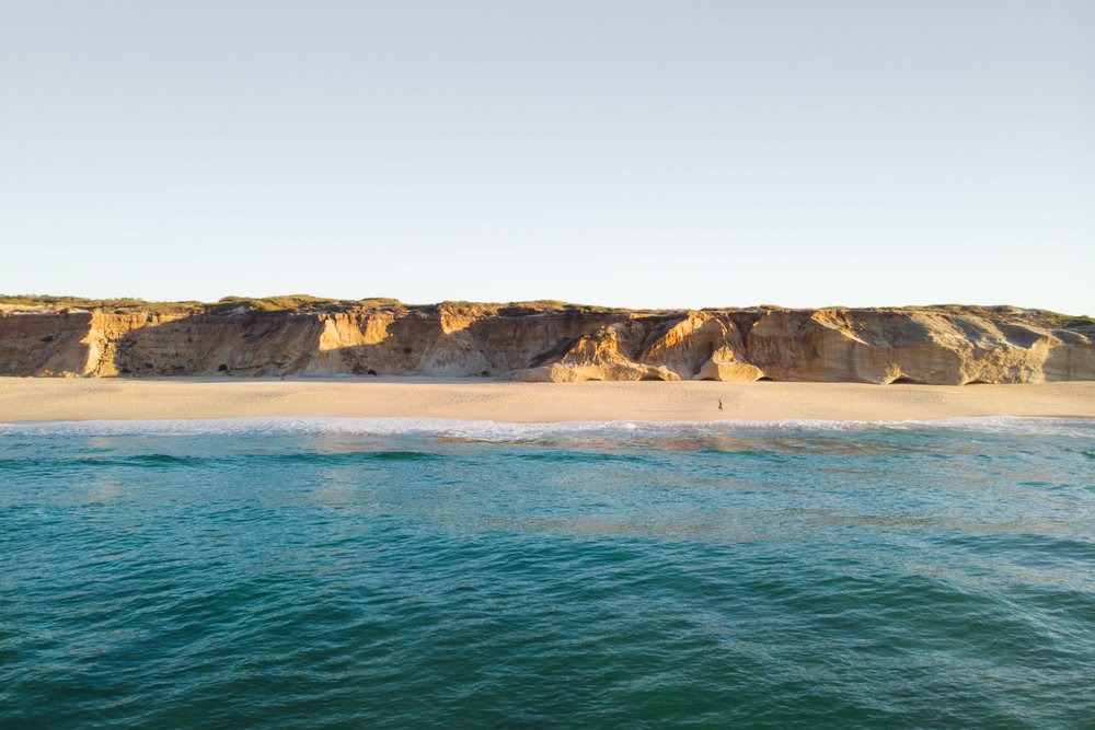 Ocean, sand and cliffs at sunset.