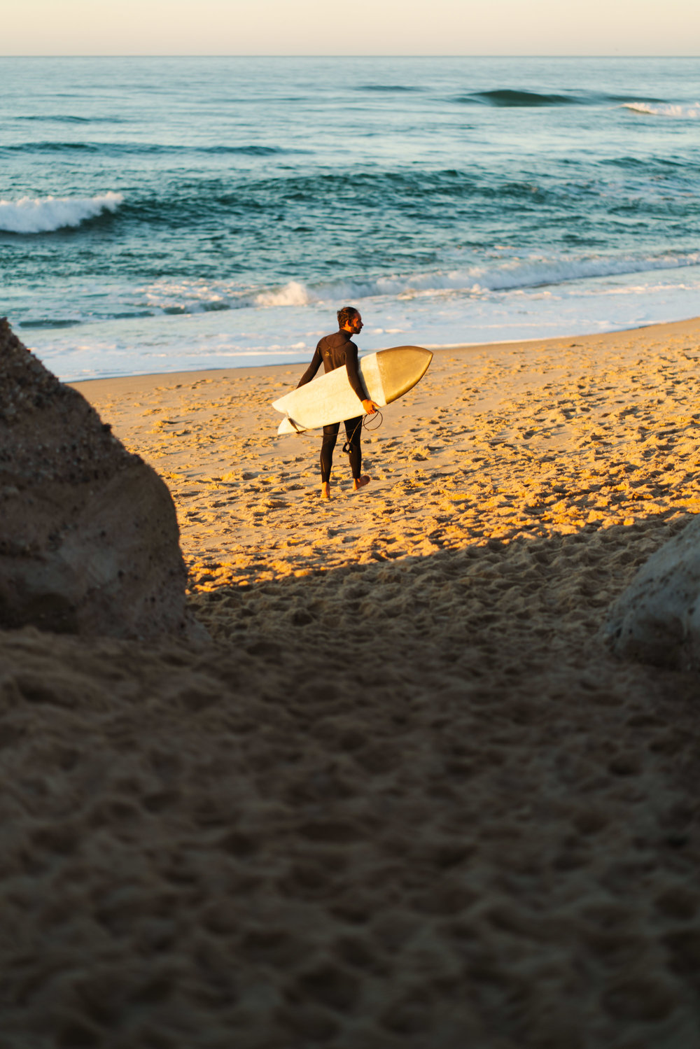 Surfer in the sand between the rocks at sunset.